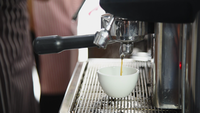 Barista preparing beverage from machine to make coffee