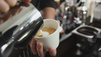 Barista pouring milk on latte coffee