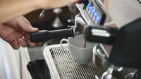 Barista preparing beverage from coffee machine
