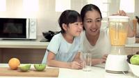 Woman and Little Girl Making Orange Smoothie with Electric Blender.