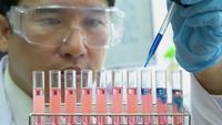 Hombre asiático experimentando con productos químicos en el laboratorio de ciencias.