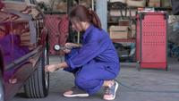 Woman Technician Checking Car Tire Air Pressure