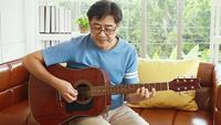 Elderly Asian Man Playing Guitar