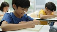 Aprendizaje y escritura de estudiantes asiáticos en el aula de la escuela.