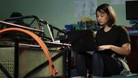 Ingénieur femme mettant à jour le logiciel sur un ordinateur portable au garage.