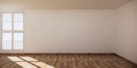 Una gran sala abierta con paredes blancas, piso de madera veteada y dos ventanas