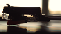 A vinyl recordplayer needlehead from a side perspective during sunset