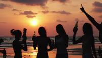 Silhouette of group drinking with a sunset background.