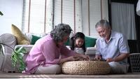 Família asiática feliz jogando jogos de quebra-cabeça em casa.