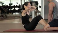 Athletic Woman Doing Sit Up Crunch mit einem Personal Trainer