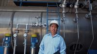 Stående som sköt av en asiatisk säker senioringenjör eller mekaniker framför bränslekraftbehållaren