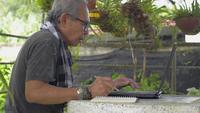 Asiatischer älterer Mann, der Laptop benutzt und auf Notizblock schreibt