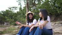 Mujeres sentadas hablando juntas sobre una roca