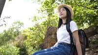 Mooie Aziatische vrouw backpacken zitten en ontspannen in de natuur