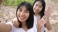 Deux jeunes femmes asiatiques souriantes prenant une vidéo de selfie