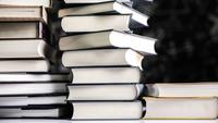 Stoppen Sie das Bewegungsstapeln von Büchern auf einem Tafelhintergrund.