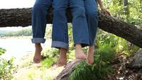 Twee meisjes zwaaien met hun voeten op een grote tak