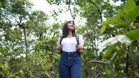 Viajero mujer asiática mirando alrededor del bosque