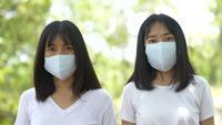 Dos jóvenes mujeres asiáticas con máscara facial protectora en el bosque