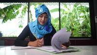 Mujer árabe de negocios trabajando con documentos en casa