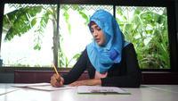 Femme musulmane d'affaires vérifiant le rapport financier
