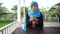 Femme musulmane nettoyer les mains par un gel d'alcool