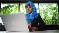Jeune femme d'affaires arabe travaillant sur ordinateur à la maison