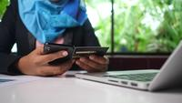 Mains féminines du titulaire de la carte de crédit faisant le paiement en ligne de la banque électronique