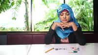 Mujer joven árabe seria sentada a la mesa con documento de resumen