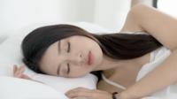 Ung kvinna som sover på sängen.