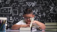 Asiatisches Kind in Gläsern liest am Schreibtisch sitzend