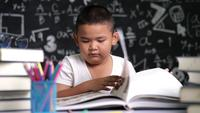 Asian child opening a book and reading