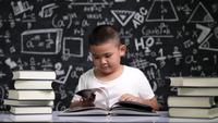 Niño de escuela asiática sentado en el escritorio y leyendo un libro