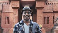 Afrikansk manlig turist som ler på kameran