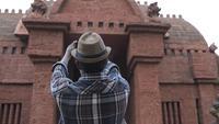 Ung manlig turist som tar bilder med en smartphone.