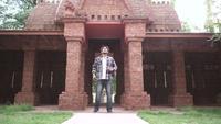 Aufgeregter afroamerikanischer männlicher Tourist betritt einen großen Tempel.