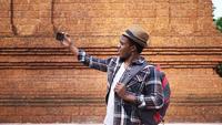 Hombre negro feliz hablando a la cámara del teléfono de pie junto al templo