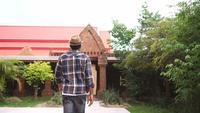Turista masculino africano caminando hacia el templo asiático.