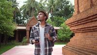 Främre sikt av afrikansk manlig turist som besöker en Thailand tempel