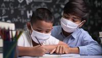 Joven maestra con una máscara enseña a los niños a escribir letras en el aula