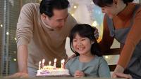 Girl Blows Candles with Family at Home