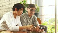 Vater und Sohn spielen glücklich ein Spiel zusammen