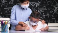 Asian teacher wearing a mask helps a boy as he writes letters.