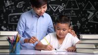 El profesor asiático está ayudando al colegial a escribir el alfabeto.