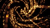 Lumières Bokeh dorées formant des spirales tournant dans l'espace