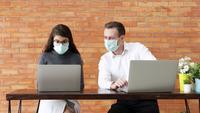 Una pareja usando máscaras faciales y trabajando en computadoras portátiles