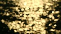 Reflejo borroso de luz dorada en el agua