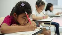 Asiatisches Mädchen, das im Klassenzimmer an der Schule schreibt.