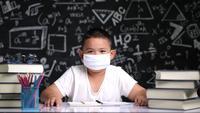 Niño de la escuela con una máscara en el aula