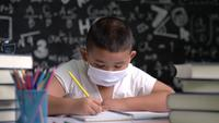 A Boy Wearing a Mask Is Learning to Write